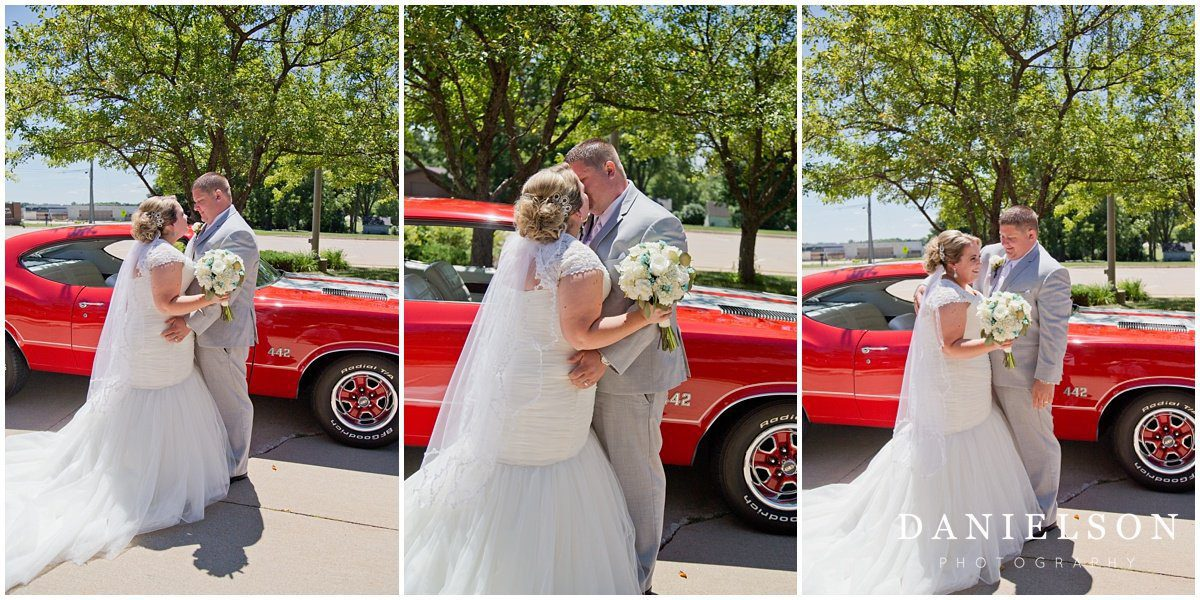 Waterloo IA wedding photographer photographs a first look between a bride and groom by the groom's classic red car in front of Our Redeemer Lutheran Church in Waverly Iowa.