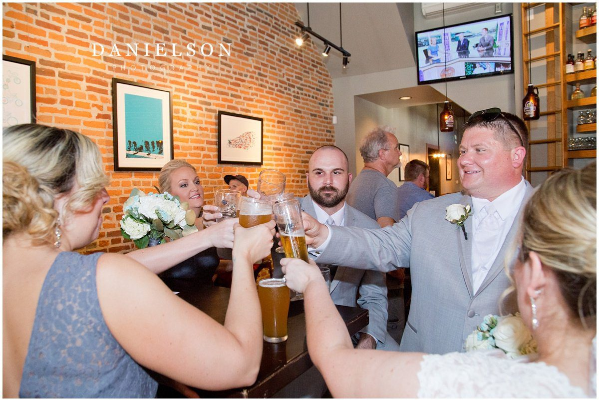 Wedding party celebrating at Single Speed Brewery in downtown Cedar Falls Iowa, photographed by Waterloo IA wedding photographer, Danielson Photography.